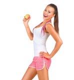 Sportig flicka som rymmer ett äpple Arkivbilder
