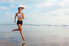 Sportig flickaspring förbi stranden längs havsbränning arkivbilder