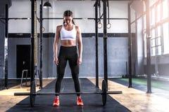 Sportig idrotts- kvinna i crossfitidrottshall Royaltyfri Fotografi
