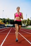 Sportig konditionkvinna som joggar på rött rinnande spår i stadion Utbildningssommar utomhus på rinnande spårlinje med gräsplan Fotografering för Bildbyråer