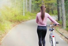 Sportig kvinna för sund livsstil på cykeln i skog arkivfoto