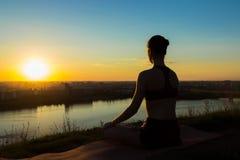 Sportig kvinna i lotusblommaposition i parkera på solnedgången Royaltyfri Fotografi
