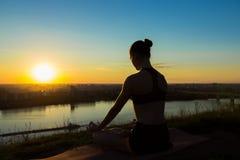 Sportig kvinna i lotusblommaposition i parkera på solnedgången Royaltyfri Foto