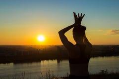 Sportig kvinna i lotusblommaposition i parkera på solnedgången Arkivbilder