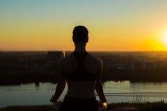 Sportig kvinna i lotusblommaposition i parkera på solnedgången Arkivbild