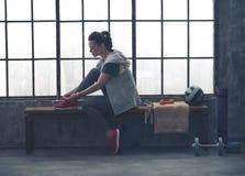 Sportig kvinna i profilsammanträde på bänken som binder skon i vindidrottshall Fotografering för Bildbyråer