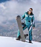 Sportig kvinna med snowboarden Fotografering för Bildbyråer