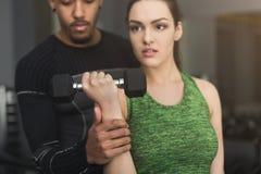 Sportig kvinna som övar med hennes personliga instruktör Royaltyfri Bild