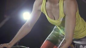Sportig kvinna som övar på velosimulator i konditionklubban arkivfilmer