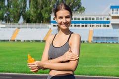 Sportig kvinna som applicerar sunscreen på stadion för körning Sportar och sunt begrepp royaltyfri fotografi