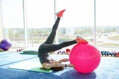 Sportig kvinna som gör pressövningar med den färdiga bollen i idrottshall Begrepp: livsstil, kondition, aerobics och h?lsa royaltyfri foto
