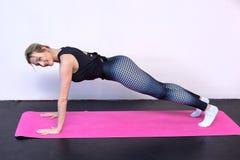 Sportig kvinna som gör yogaövningar i en idrottshall arkivfoto