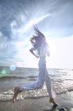 Sportig kvinna som kör i havskust Arkivfoto