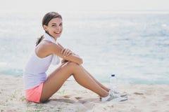 Sportig kvinna som ler, medan sitta på sanden efter genomkörare royaltyfria bilder