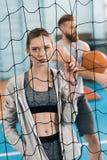 Sportig kvinna som netto ser kameran till och med volleyboll Arkivbilder