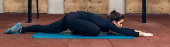 Sportig kvinna som sträcker benet på golvet Arkivbilder