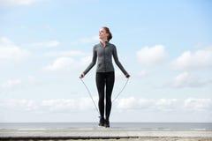 Sportig kvinna som värmer upp med hopprepet Fotografering för Bildbyråer
