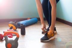 Sportig kvinnagenomkörare hemma, fokus på band av skor royaltyfri fotografi