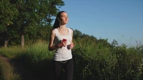 Sportig kvinnaspring för ung brunnete i parkera Henne som lyssnar till musiken stock video