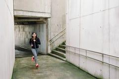 Sportig kvinnaspring i staden arkivfoton
