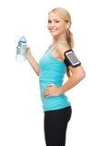 Sportig kvinnaspring med smartphonen och hörlurar Arkivfoton