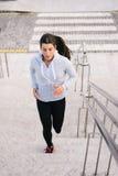 Sportig kvinnaspring- och klättringtrappa arkivbild