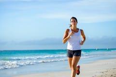 Sportig kvinnaspring på den tropiska stranden arkivbild