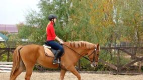 Sportig kvinnlig jockeyövningsridning arkivfoto