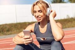 Sportig livsstil Ung kvinna i hörlurar på stadion som sitter på chosing sång för spår på lycklig lyssnande musik för smartphone arkivfoto