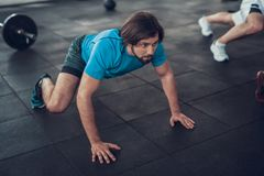 Sportig man i blåa T-skjortakrypanden på idrottshallgolv arkivbilder