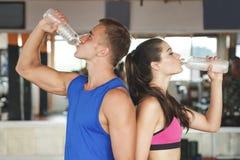 Sportig man och kvinna som tillbaka dricker mineralvatten för att dra tillbaka Arkivfoto