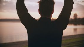 sportig man som 4K värmer upp nära den tysta solnedgångfloden Svängande armar för tillbaka sikt och hoppa nära härlig flodpanoram stock video