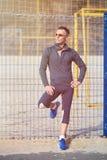Sportig man som poserar på en rasterbakgrund royaltyfri bild