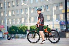 Sportig manlig cyklist som poserar nära cykeln i centrum royaltyfri fotografi