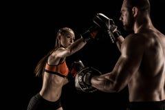 Sportig muskulös ung man och kvinna som tillsammans boxas royaltyfria bilder