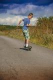 Sportig pojkeridning på vägwaveborden Royaltyfria Bilder
