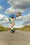 Sportig pojkeridning på vägwaveborden Royaltyfria Foton