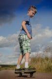 Sportig pojkeridning på vägwaveborden Arkivfoto