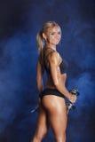 Sportig sexig flicka med hantelstudiofotoet på rökbakgrund Royaltyfri Bild