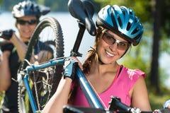 Sportig tonår som bär deras mountainbiken Royaltyfri Foto
