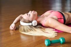 Sportig ung kvinna med långt blont hår som kopplar av att ligga på sportar som är matta på trägolvet i idrottshallen arkivbilder