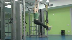 Sportig ung kvinna som gör övning på idrottshallen arkivfilmer