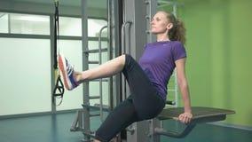 Sportig ung kvinna som gör övning på idrottshallen lager videofilmer