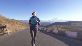 Sportig ung muslimkvinna i en halsdukspring på den soliga bergvägen, långsam mo stock video