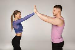 Sportiga attraktiva par i den moderiktiga sportswearen som till varandra ger höga fem royaltyfri bild