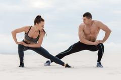 Sportiga konditionpar som gör sträcka övningar utomhus Härlig idrotts- man och kvinna arkivbild