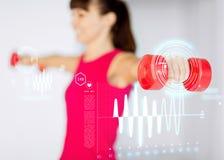 Sportiga kvinnahänder med ljusröda hantlar royaltyfri foto