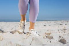 Sportiga kvinnas fot på sanden arkivfoto