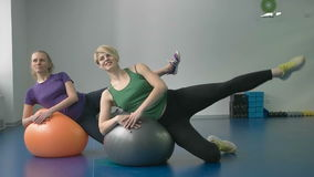 Sportiga kvinnor som gör gymnastiska övningar eller övar i konditiongrupp arkivfilmer