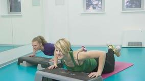 Sportiga kvinnor som gör gymnastiska övningar eller övar i konditiongrupp lager videofilmer